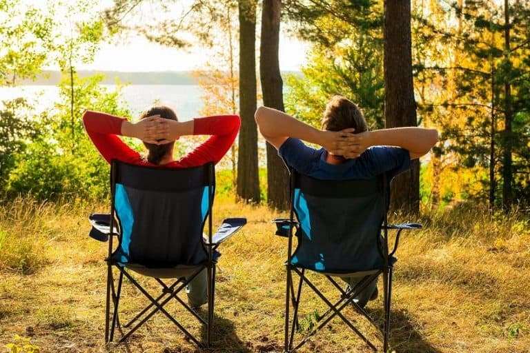 two guys sitting on a camping chair