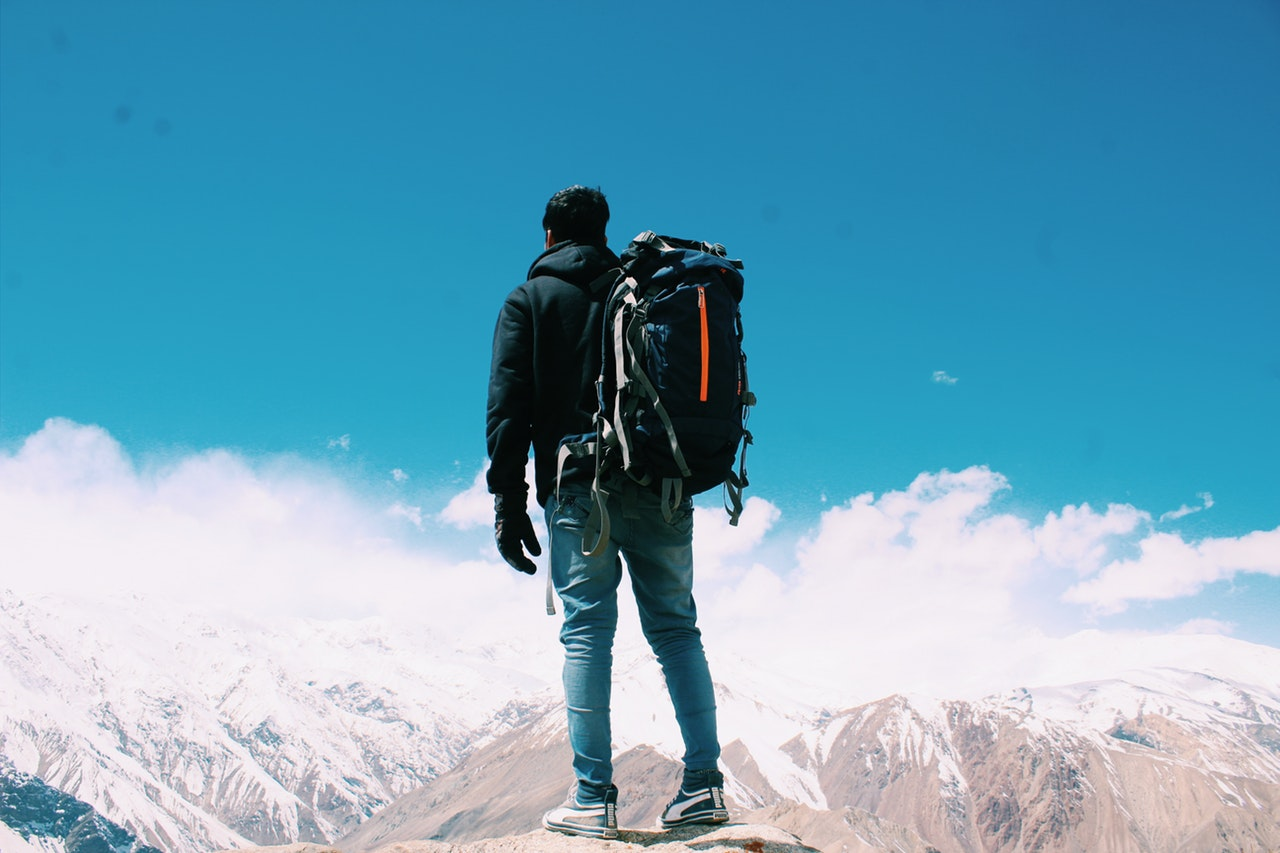 man with backpack standing on top of mountain