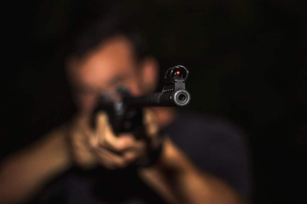 Blurred man holding a rifle aimed at the camera